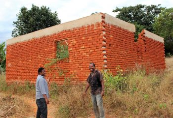 A happy Bakari (right) standing infront of his new house with James, who helped him secure his rights