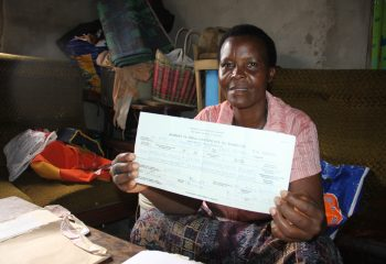 Mrs. Wilgester Milinga showing her marriage certificate she had submitted to Yombo Vituka paralegals centre in Temeke