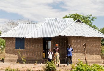 Msomi Simtandi, now 10, standing infront of their new house with elder sister. Zuhra who is now his caretaker
